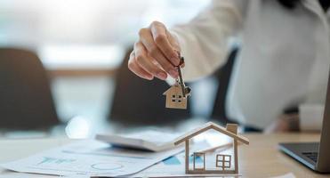 agente immobiliare che tiene la chiave di casa al suo cliente dopo aver firmato il contratto, concetto di immobile, trasloco o affitto di proprietà foto