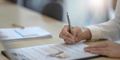 primo piano donna che firma contratto, contratto di lavoro, cliente femminile che mette la firma su documenti legali, prendendo prestiti o mutui, acquistare immobili, assicurazioni o accordi di investimento foto