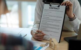 contratto di vendita di acquisto per l'acquisto di una casa, l'agente immobiliare presenta il mutuo per la casa e fornisce le chiavi al cliente dopo aver firmato il contratto per l'acquisto di una casa con modulo di domanda di proprietà approvato foto
