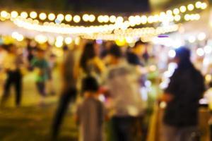 astratto sfondo sfocato di persone che fanno shopping al festival notturno foto