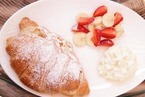 tagliare fragole e banana fresche con rotolo e crema sul piatto per colazione foto