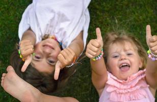 due bambine sdraiate sull'erba, ridendo e mostrando i pollici in su foto