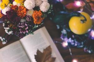 vista dall'alto di un mazzo di fiori e un libro aperto sul tavolo foto
