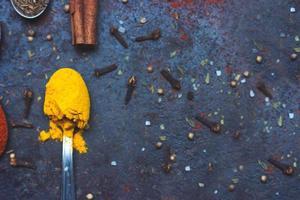 cucchiaino da tè pieno di spezie al curry, su sfondo nero con spazio di copia foto