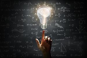 mano che tiene un cervello all'interno di una lampadina sulla lavagna a muro foto