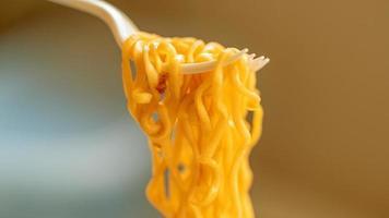 mangiare noodle istantanei usando una forchetta di plastica su sfondo bokeh foto