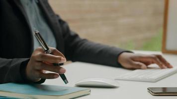 Close up della donna che lavora con la tastiera del computer e la penna foto