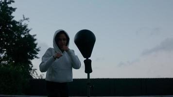donna matura che indossa top con cappuccio utilizzando punch ball foto