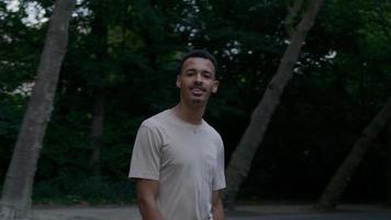 ritratto di giovane uomo che cammina nel parco guardando la fotocamera foto