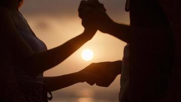 ritratto di giovane coppia che si tiene per mano sulla spiaggia foto