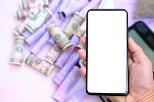 mano che tiene smartphone con soldi sul tavolo e spazio di lavoro, business e tecnologia concept foto