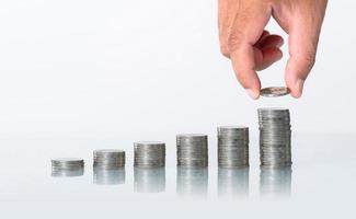 il concetto di risparmio di denaro, mettendo a mano la pila di monete di denaro che cresce su sfondo bianco foto