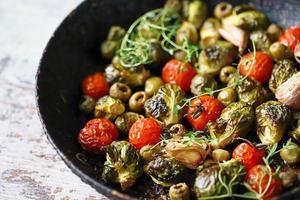 cavolini di bruxelles con verdure ed erbe in padella foto