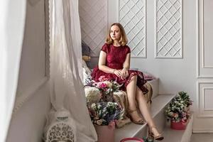 una ragazza carina ed elegante in un elegante abito bordeaux si siede vicino alla finestra nella sua stanza. adolescente. laurea a scuola, università foto