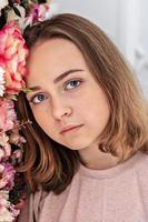 ritratto di una giovane ragazza al muro con fiori. foto