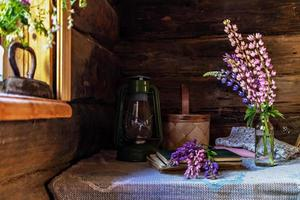 natura morta di oggetti vintage e un mazzo di lupini su un tavolo vicino alla finestra in una vecchia casa di paese. foto
