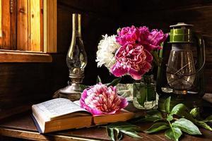 natura morta di oggetti vintage e un bouquet di peonie su un tavolo vicino alla finestra in una vecchia casa di paese. foto