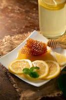 succo di limone con miele su tavola di legno limoni e foglie di salvia foto