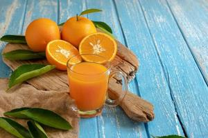 arancia fresca e un bicchiere di succo d'arancia su uno sfondo di tavolo in legno foto