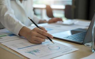 primo piano uomo d'affari che utilizza calcolatrice e laptop per calcolare finanza, tasse, contabilità, statistiche e concetto di ricerca analitica foto