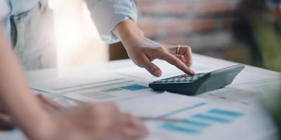 donna d'affari che utilizza la calcolatrice per fare finanza matematica sulla scrivania di legno in ufficio e lavoro aziendale sfondo, tasse, contabilità, statistiche e concetto di ricerca analitica foto