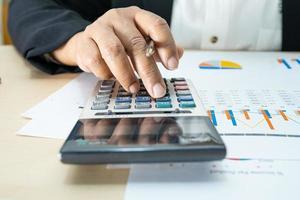 contabile asiatico che lavora e analizza i rapporti finanziari contabilità del progetto con grafico grafico e calcolatrice in ufficio moderno, finanza e concetto di business. foto
