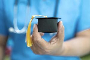 lo studio medico asiatico impara con il cappello di divario di laurea nel concetto di medicina dell'educazione geniale brillante intelligente del reparto ospedaliero. foto