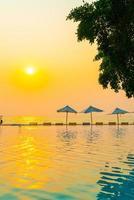 ombrellone e sdraio intorno alla piscina con vista mare oceano foto