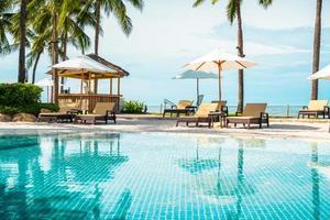 bellissima spiaggia tropicale e mare con ombrellone e sedia intorno alla piscina nel resort dell'hotel foto