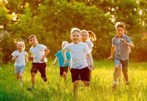 un gruppo di bambini felici di ragazzi e ragazze corrono nel parco sull'erba in una soleggiata giornata estiva. foto