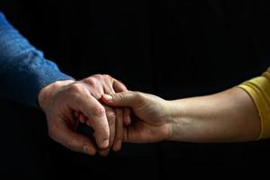giovane coppia che si tiene per mano mostrando amore e cura, marito e moglie sono teneramente vicini, mostrando sostegno e comprensione foto