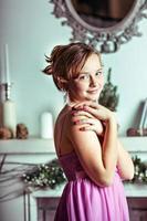 una giovane ragazza in un abito rosa sullo sfondo di decorazioni natalizie e un caminetto nella stanza foto