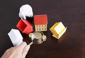 concetto di prestiti ipotecari con casa di carta e pila di monete foto