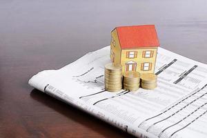 concetto di investimento immobiliare con casa di carta e pila di monete su carta di notizie su tavola di legno foto