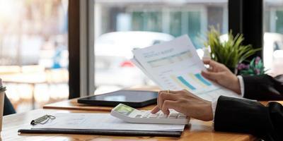 donna con relazione finanziaria e calcolatrice. donna che usa la calcolatrice per calcolare il rapporto al tavolo in ufficio foto