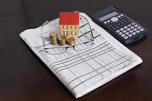concetto di prestiti ipotecari con casa di carta con pila di monete, occhiali e giornali, calcolatrice foto