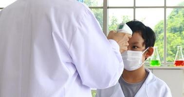 gli insegnanti stanno usando un termometro frontale a infrarossi per controllare la temperatura di uno studente maschio prima di andare a lezione per i sintomi del covid-19. concetto di prevenzione dell'epidemia foto