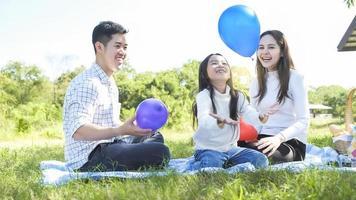 ritratto asiatico viaggio di famiglia padre madre e figlia godersi il relax giocando a palloncini con la famiglia allo stile di vita libertà vacanza in famiglia caucasico asiatico. viaggio di un giorno nuovo normol coronavirus covid 19 foto