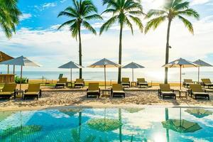 bellissimo ombrellone di lusso e sedia intorno alla piscina all'aperto in hotel e resort con palme da cocco su cielo blu foto