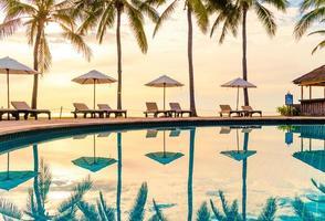 ombrellone e sedia intorno alla piscina in hotel resort per viaggi di piacere e vacanze vicino alla spiaggia dell'oceano del mare foto
