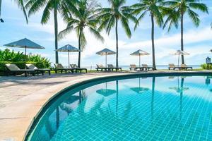 bellissimo ombrellone e sedia intorno alla piscina in hotel e resort foto