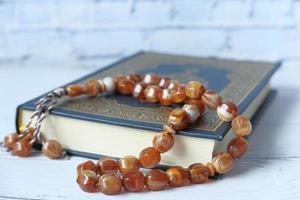 libro sacro corano e rosario sul tavolo, primo piano. foto