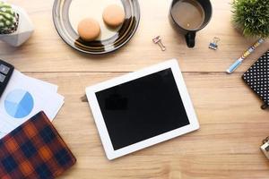 composizione piatta di tavoletta digitale e cancelleria per ufficio su sfondo nero foto