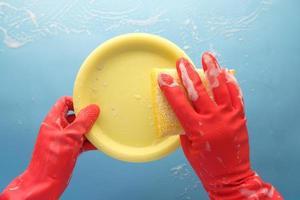 spugna, guanti di gomma e piastra colorata su blu foto