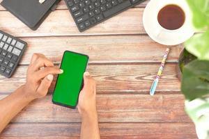 vista dall'alto della mano dell'uomo utilizzando smart phone sulla scrivania in ufficio foto
