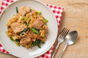 spaghetti di riso saltati in padella con salsa di soia nera e maiale e cavolo riccio foto