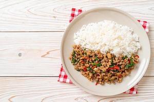 basilico tailandese saltato in padella con carne di maiale macinata su riso guarnito foto