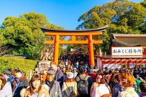 kyoto, giappone - 11 gennaio 2020 - porte torii rosse a fushimi inari taisha con turisti e studenti giapponesi. fushimi inari è il santuario shintoista più importante. foto