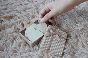 Immagine ravvicinata di mani femminili che tengono un piccolo regalo. piccolo regalo nelle mani di una donna indoor. foto