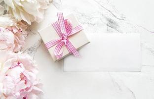 peonie rosa con carta vuota e confezione regalo su sfondo di marmo bianco foto